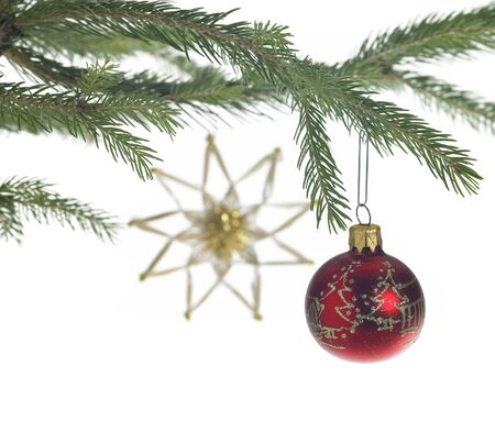 Studio photography of some christmas decoration with red christmas bauble on fir branch and a blurry straw star in the back photo