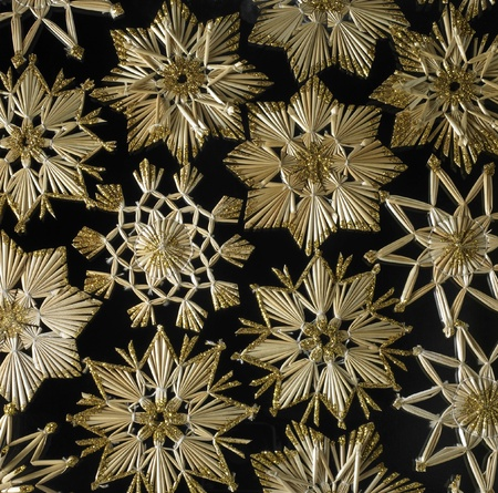 full frame studio photography showing a christmas background with gold toned straw stars in black back photo