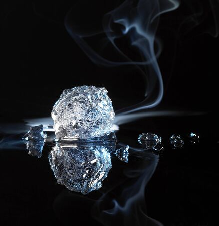moistness: studio photography of a ice crystal and smoke in black reflective back