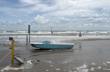 ebb: green boat on the beach at ebb tide in Southern Italy