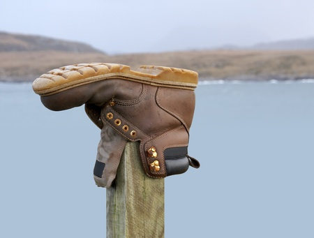 imposed: shoe on a wooden stack and blurry scottish landscape in the back Stock Photo
