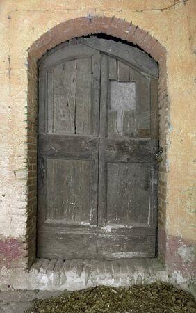 old rundown wooden door on stone facade photo