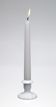 candle holder: Studio shot of a a white burning candle and a white porcelain candle holder in light back