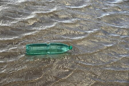 pollution theme with a green plastic bottle floating on water surface photo