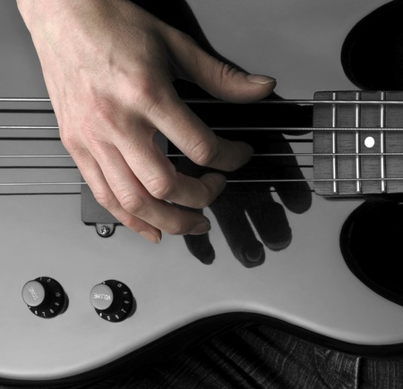 reflectance: female hand on the detail of a black bass guitar in dark back
