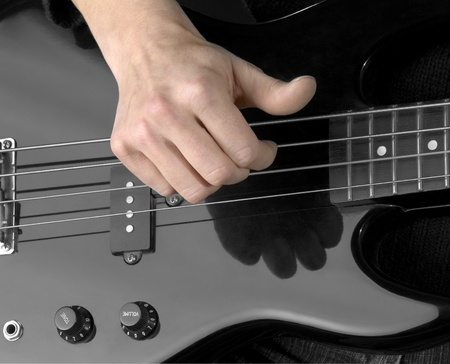 reflectance: detail of a black bass guitar and hand in dark back