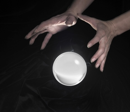 high angle shot of a glowing crystal ball surrounded by black crinkly fabrics and two hands around photo