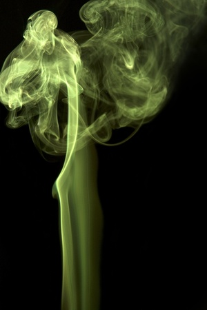 precipitate: abstract picture showing some vibrant yellow and green colored smoke in black back Stock Photo
