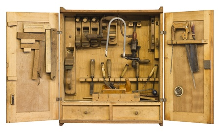 woodworking: old historic tool cabinet filled woth woodworking tools.Frontal shot with open doors in white back with clipping path