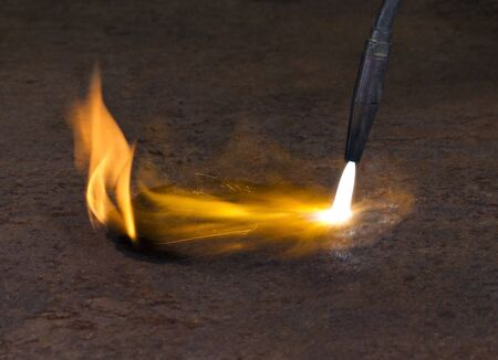 welding torch tip and dashing flame on rusty metallic ground photo
