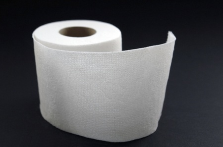 studio photography of a white toilet paper roll in dark back photo