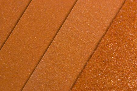 様々 な穀物のいくつかのオレンジ色のサンドペーパーを示す抽象的な背景 写真素材