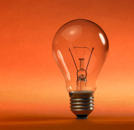 studio photography of a upright clear electric bulb in orange and red back photo