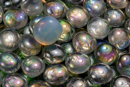 full frame abstract background picture with iridescent glass beads in dark back photo
