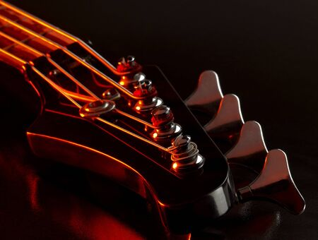 fretboard: detail of a bass guitar with red light in dark back