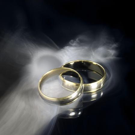 wedding  ring: Fotografía de estudio de dos anillos de boda oro y humo en negra espalda reflectante