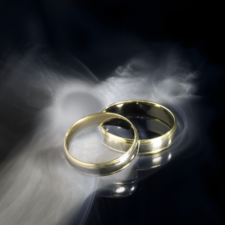 wedding ring: studio photography of two golden wedding rings and smoke in black reflective back
