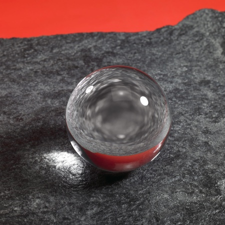 magical equipment: a clear crystal ball on rough dark grey stone surface in front of red back