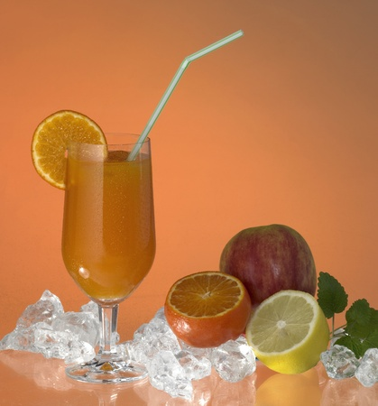 commercialization: studio photography showing a stemware glass filled with fruit juice, sliced orange and drinking straw, located in orange background with some fruits and crushed ice