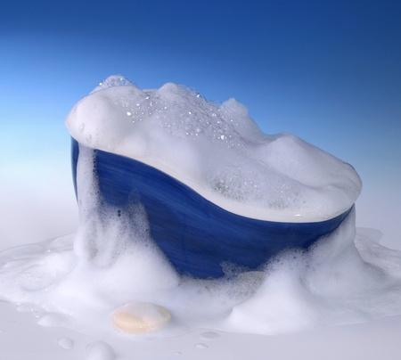 schiuma di sapone: simbolico di pulizia e lavaggio di fondo con vasca da bagno, sapone e un sacco di schiuma sul retro blu sfumato Archivio Fotografico
