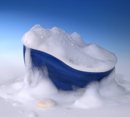 foam: symbolic cleaning and washing background with bathtub,soap and lots of foam in blue gradient back