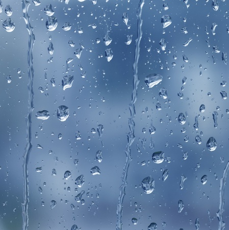 glass panel: abstract full frame background showing a window with raindrops rolling off (blue toned)