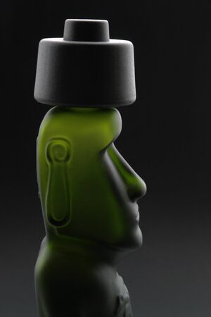 head of a moai-styled bottle in dark back photo