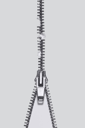 undone: symbolic studio photography of a damaged zipper in light back, seen from above