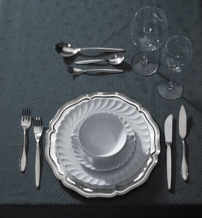 festive place setting with flatware, whiteware and drinking glasses, seen from above photo