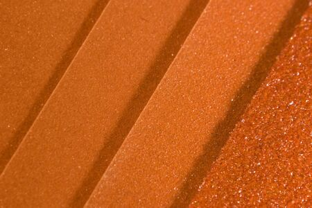 sandpaper: abstract background with orange toned sandpaper in various grains