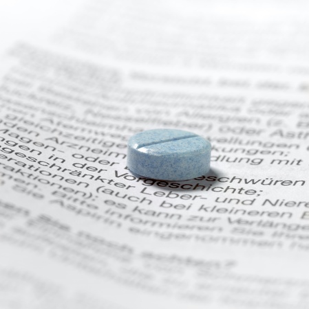 adverse reaction: studio shot of a blue pill on package insert