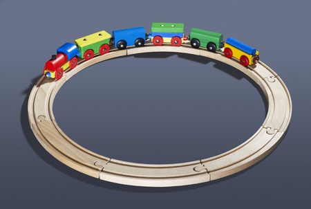 wood railroad: studio photography of a colorful wooden toy train on a track circle in dark back Stock Photo