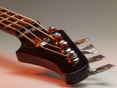 worm gear: detail of a bass guitar with red light in grey back