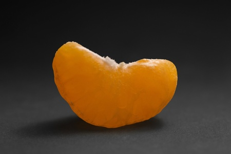 agleam: studio photography of a tangerine cut in dark back