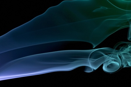 particulates: abstract picture showing some colorful blue and green smoke in black back