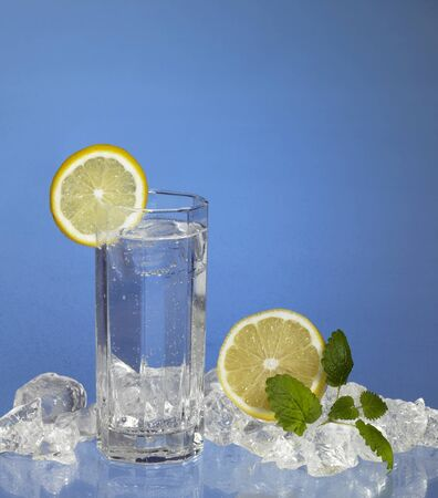 commercialization: studio photography of a glass with transparent refreshment drink, located in blue fresh ambiance with lemons and ice cubes