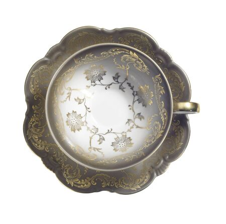 out dated: studio photography of a empty nostalgic tea cup with golden ornaments seen from above, isolated on white