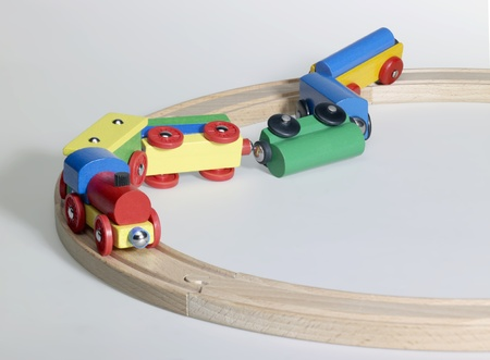 studio photography of a colorful wooden toy train on wooden tracks while having a accident, in light back photo