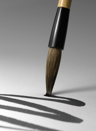 writing instrument: detail of a chinese brush while drawing a line in light back Stock Photo