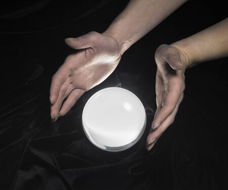 high angle shot of a glowing crystal ball surrounded by black crinkly fabrics and two hands around Stock Photo - 10987509