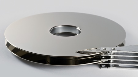 detail shot of a separated hard disk platter with actuator arm in light grey back photo
