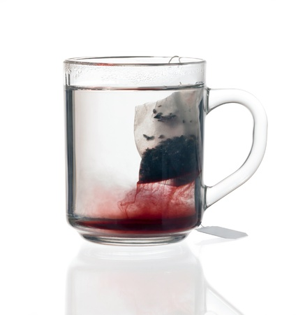 transparent glass teacup including reddish fluid with tea bag, on reflective groung isolated on white with clipping path Stock Photo - 10987176