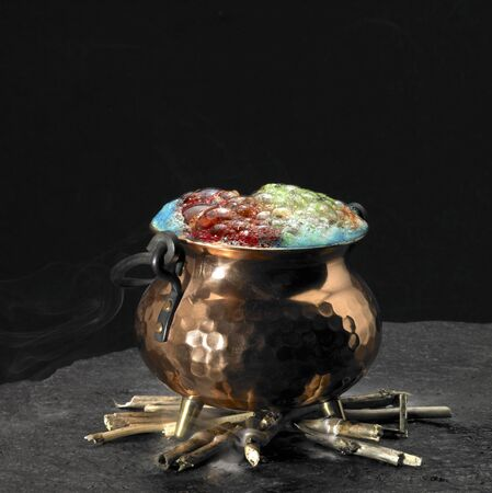 magical equipment: symbolic picture with spumous potion and copper cauldron on a fireplace