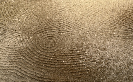 art theme showing a abstract lined owl shape pressed in sand surface Stock Photo