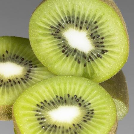 moistness: girato in studio di un particolare arrangiamento di frutta fresca kiwi a fette sul retro riflettente grigio