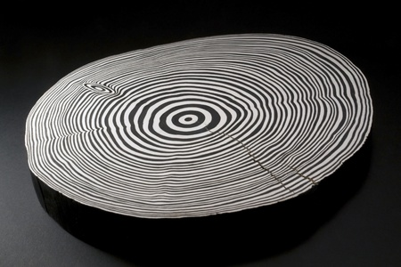 piece of wood with black and white painted annual rings in dark back Фото со стока