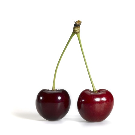 Studio photography of a shiny pair of cherries isolated on white with shadow photo