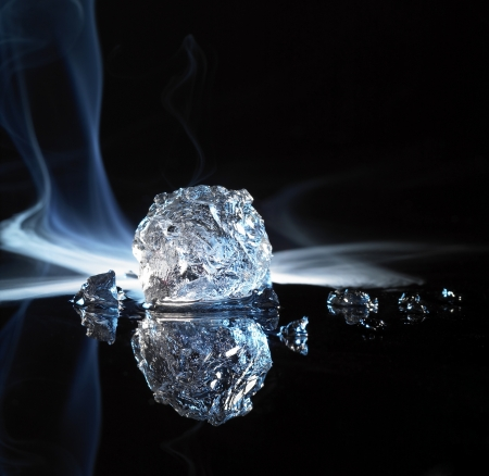 studio photography of a ice crystal and smoke in black reflective back