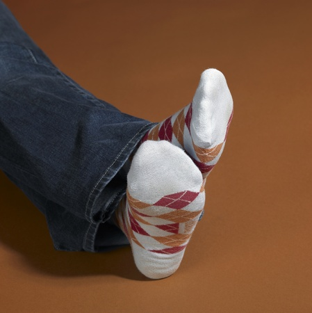 accouterment: a pair of resting feet in colorful socks and brown background