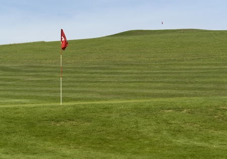 level playing field: detail of a golf course in Southern Germany with near and distant flag in green back